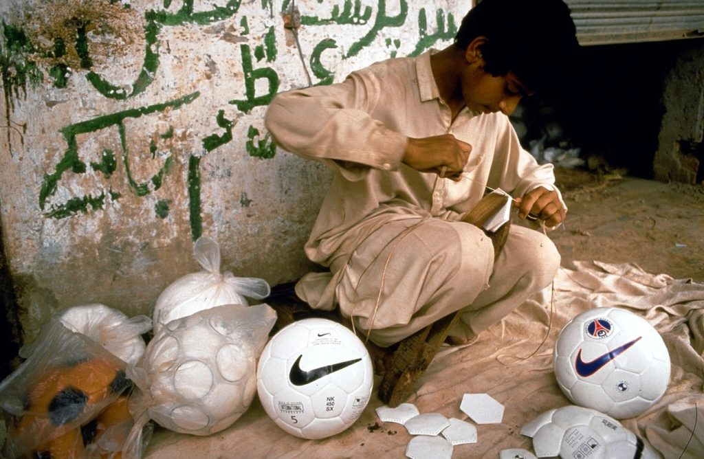 A boy sewing Nike soccer balls